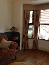 hard pelmet curtains with tie backs on bay fronted window clares