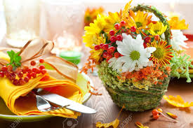 autumnal place setting with backet of autumn flowers stock photo