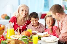 portrait of happy family gathered at festive table on thanksgiving