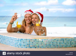 couple in swimming pool with santa hats holding cocktails stock
