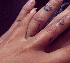 black outline queen and king crown tattoo on couple finger