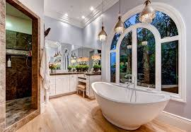 beautiful master bath with tub and pendant lights with hanging glass
