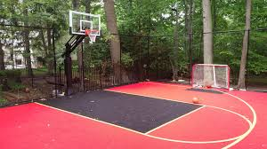 this is a forest green and red concrete backyard basketball court