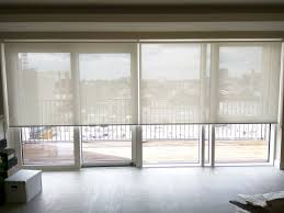 sunscreen roller blinds over bi fold doors in living room