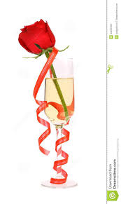 red rose in glass of champagne and paper streamer royalty free