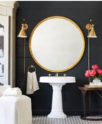 gorgeous gold round mirror and brass wall sconces in this modern