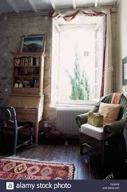 French Country Livingroom Cushions On Green Wicker Chair Beside Window In French Country