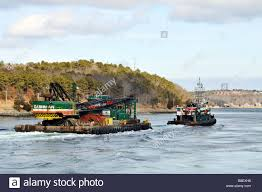 tugboat towing a barge with crane and heavy equipment from cashman