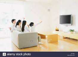Office In The Living Room Family Of Four People Watching Tv On The Sofa In The Living Room