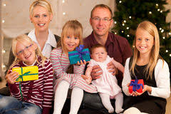 family opening presents in front of tree stock image