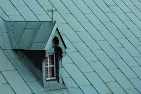 highly regarded green slate roofing with gothic attic window as