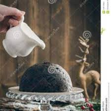 christmas pudding in snowy setting with creative lighting stock