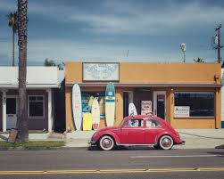 volkswagen red car red volkswagen infron of a surf board store free image peakpx