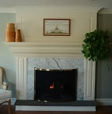 white stained wooden fireplace mantel above white glass mosaic