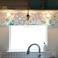 what a great idea globe string lights above the kitchen sink