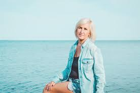 middle age women with blue hair blonde middle age woman in jeans shirt sitting on a beach with