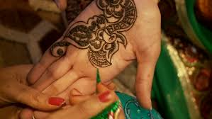 a tattoo master mehendi artist makes drawing of henna