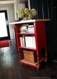 an antique radio stand converted into a red kitchen island a