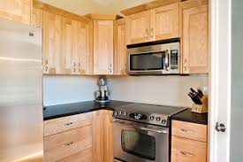 wooden birch cabinets with black counter tops to match flooring