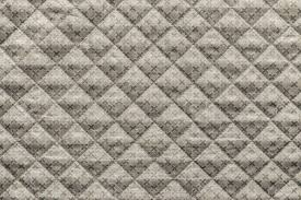 grained texture of beige quilted fabric with an abstract pattern