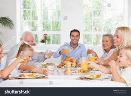 smiling family toasting thanksgiving dinner table stock photo