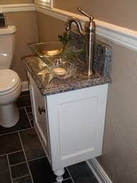 luxurious white small vanity and glass bowl sink on gray marble