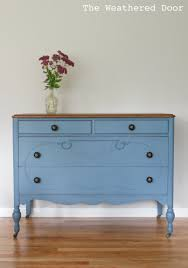 a smokey blue dresser with a stained top the weathered door
