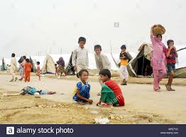 flood affected children play in front of makeshift tent houses at