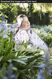 side view of a cute young in fairy costume sitting at flower