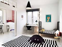 toddler bedroom with black bed frame and black white area rug