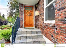 house with brick trim entrance porch with orange door stock photo