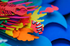 colorful layered paper cut poster depicting ocean pollution by