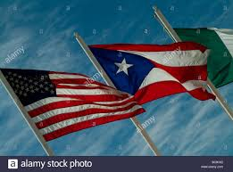 american puerto rican and italian flags waving against a blue sky