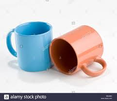 two pastel ceramic coffee mugs with one tipped over stock photo