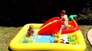 kids having fun on a backyard inflatable pool with water slide