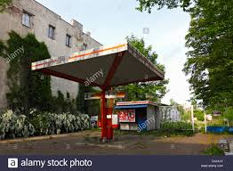 neglected gas station and building covered in climbing plants in