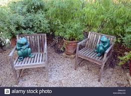 garden chairs ornamental frogs in gravel patio garden