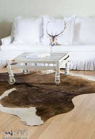 Cow Home Decor Chandeliers And Cow Hide Rugs In White Living Room Decor Hometalk