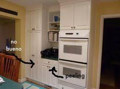 Kitchen Cabinet Redo by Peeling Patching And Painting Laminate Cabinets