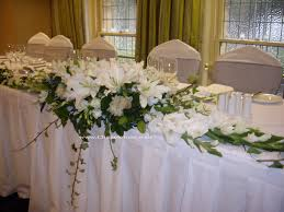 cheap wedding reception ideas large table with white tablecloth combined by white flower bouquet