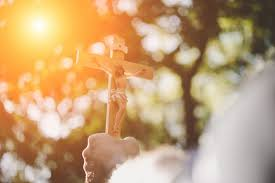 holding wooden jesus cross into the sky with