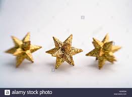 three gold star christmas ornaments in row blurred on edges with