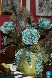 a floral arrangement consisting of hydrangeas peacock feathers
