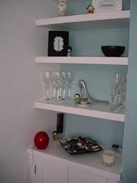 white floating shelves in the alcove with different color behind