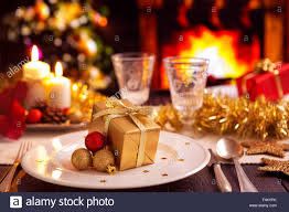 a romantic christmas dinner table setting with candles and a romantic christmas dinner table setting with candles and christmas decorations a fire is burning
