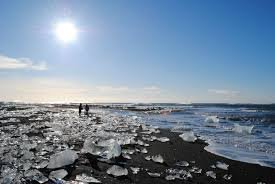 broken up glacial ice on a volcanic black sand beach in iceland