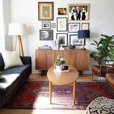 midcentury modern living room with oval table on persian rug also