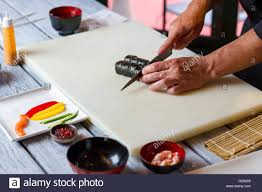 Cooking Board by Hand With Knife Cutting Sushi Sushi On Beige Cooking Board Cafe