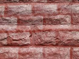textured concrete block wall painted to look like red bricks