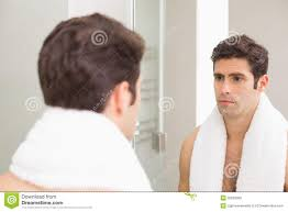 Looking In The Mirror Meme - tensed young man looking at self in bathroom mirror stock image